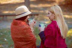 Due giovani ragazze caucasiche che godono del caffè in parco autunnale immagine stock