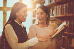 Due giovani ragazze degli studenti al libro di lettura delle biblioteche Fotografia Stock Libera da Diritti