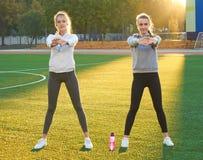 Due giovani ragazze di sport che fanno ginnastica di mattina sull'erba verde aria aperta, alba, forma fisica, salute, sport Fotografie Stock Libere da Diritti