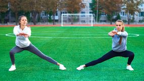 Due giovani ragazze di sport che fanno ginnastica di mattina sull'erba verde aria aperta, alba, forma fisica, salute, sport Immagini Stock