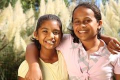 Due giovani ragazze felici del banco nell'abbraccio di amicizia Immagine Stock