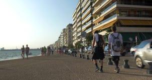 Due giovani ragazzi camminano lungo il lungonmare di Salonicco, Grecia stock footage