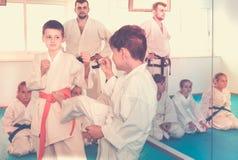 Due giovani ragazzi che si preparano nel pugilato d'allenamento alla classe di karatè Fotografia Stock