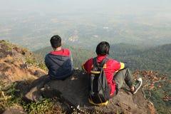 Due giovani ragazzi con lo zaino che prende seduta sulla cima di una montagna e godere della vista della valle Immagini Stock