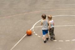 Due giovani ragazzi su un campo da pallacanestro Fotografie Stock Libere da Diritti