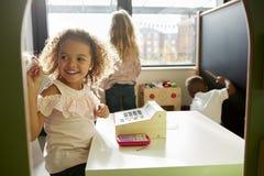 Due giovani scolare e un ragazzo che gioca insieme in una casetta per giocare alla scuola infantile, retroilluminata immagine stock libera da diritti