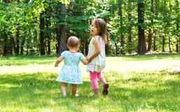 Due giovani sorelle che si tengono per mano fuori Fotografie Stock Libere da Diritti