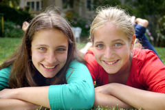 Due giovani sorelle che si trovano sull'erba Fotografia Stock