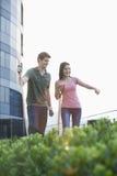 Due giovani sorridenti che fanno il giardinaggio e che indicano nelle piante in un giardino della cima del tetto nella città Immagine Stock