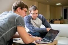Due giovani stanno discutendo un progetto nell'ufficio Sieda alla tavola accanto a ogni altro, uno di loro dice l'altro circa cia immagine stock libera da diritti