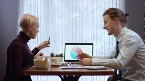 Due giovani stanno lavorando insieme e stanno discutendo i progetti in un caffè La donna e l'uomo in un ristorante o stock footage