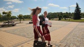 Due giovani studentesse che camminano insieme all'aperto nel parco un giorno soleggiato archivi video