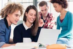 Due giovani studenti che cercano una risposta al loro bot di domanda Immagini Stock