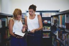 Due giovani studenti che preparano per la sessione nella biblioteca Fotografia Stock