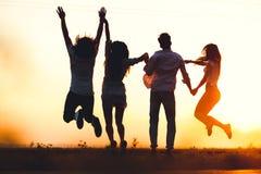 Due giovani tipi e due ragazze stanno tenendo la loro mano e stanno saltando nel campo un giorno di estate Vista posteriore fotografie stock