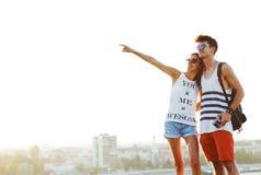 Due giovani turisti che fanno un giro turistico una città, indicante con il dito Immagine Stock