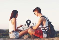 Due giovani turisti che si rilassano e che esaminano una mappa della guida Immagini Stock Libere da Diritti