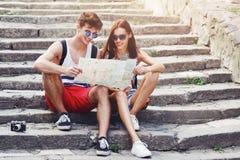 Due giovani turisti che si rilassano e che esaminano una mappa della guida in una città Immagini Stock