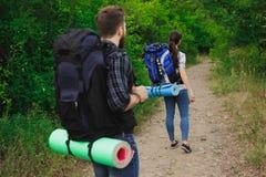 Due giovani turisti con gli zainhi Gli amici felici nel fondo del cielo blu e dell'erba, si rilassano il tempo in vacanza, viaggi immagini stock libere da diritti