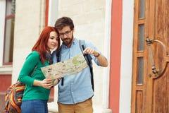 Due giovani turisti con la città facente un giro turistico degli zainhi Immagini Stock Libere da Diritti