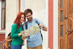 Due giovani turisti con la città facente un giro turistico degli zainhi Immagini Stock
