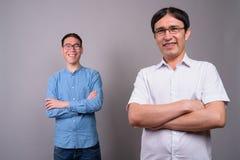 Due giovani uomini d'affari asiatici che indossano insieme gli occhiali contro immagine stock