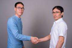 Due giovani uomini d'affari asiatici che indossano insieme gli occhiali contro fotografia stock