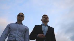 Due giovani uomini d'affari che camminano nella città con cielo blu al fondo Uomini di affari che permutano per lavorare insieme  stock footage