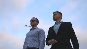 Due giovani uomini d'affari che camminano nella città con cielo blu al fondo Uomini di affari che permutano per lavorare insieme  video d archivio