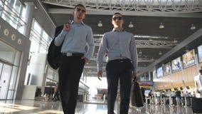 Due giovani uomini d'affari che camminano in terminale all'aeroporto ed alla conversazione Uomini che fanno un passo al centro di archivi video