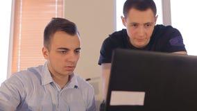 Due giovani uomini d'affari che discutono un affare proiettano in un computer portatile all'ufficio stock footage