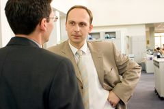 Due giovani uomini d'affari che interagiscono alla riunione nell'ufficio fotografie stock libere da diritti