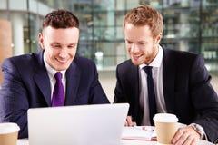 Due giovani uomini d'affari che mangiano caffè, facendo uso di un computer portatile Fotografia Stock Libera da Diritti