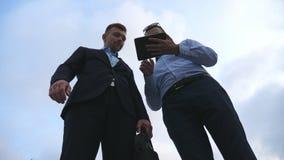 Due giovani uomini d'affari che parlano e che per mezzo del pc della compressa all'aperto Uomini di affari che lavorano alla comp Immagini Stock