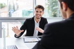 Due giovani uomini d'affari felici che si siedono e che lavorano alla riunione d'affari Fotografia Stock Libera da Diritti