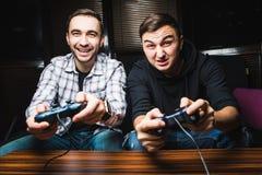 Due giovani uomini felici che giocano i video giochi Immagini Stock