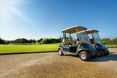 Due golf-carretti che stanno al parcheggio di estate Fotografie Stock Libere da Diritti