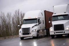 Due grandi camion dei semi degli impianti di perforazione con i rimorchi dei semi che corrono parallelamente Fotografia Stock Libera da Diritti