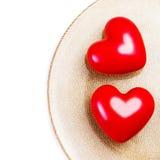 Due grandi cuori rossi su un piatto dorato isolato su backgroun bianco Immagini Stock