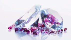 Due grandi diamanti con molte piccole gemme che girano sopra il bianco archivi video