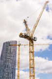 Due grandi gru di costruzione con il grattacielo ed il cielo nuvoloso Fotografia Stock