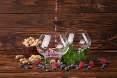 Due grandi vetri con il succo di frutta Mirtilli, lamponi, arachidi in una ciotola, menta e su un fondo di legno di marrone scuro Immagine Stock Libera da Diritti