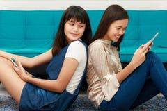 Due grils asiatici che esaminano smatphone e compressa Immagine Stock