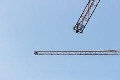 due gru a braccio girevole contro un cielo blu senza nuvole Fotografia Stock