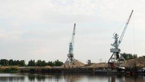Due gru del porto del carico nel porto ed in una chiatta, un fiume archivi video