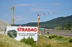 Due gru a torre che lavorano al cantiere D1 della strada principale slovacca, tabellone per le affissioni della società edificio  Immagine Stock Libera da Diritti