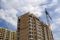 Due gru a torre che lavorano all'alta costruzione di mattone di aumento nell'ambito del const Immagini Stock Libere da Diritti