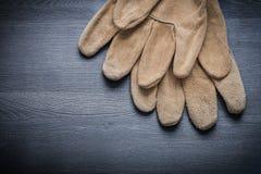 Due guanti di sicurezza sul bordo di legno scuro Fotografie Stock