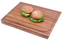 Due hamburger casalinghi del pesce e un hamburger vegetariano con differenti ingredienti sul bordo isolato su fondo bianco fotografie stock