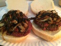 Due hamburger con le cipolle sui panini Fotografia Stock